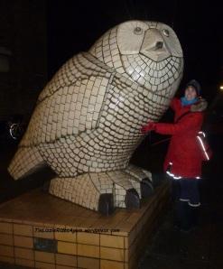 Red coat, reflective trim on skirt, purse - hugging an owl in Copenhagen