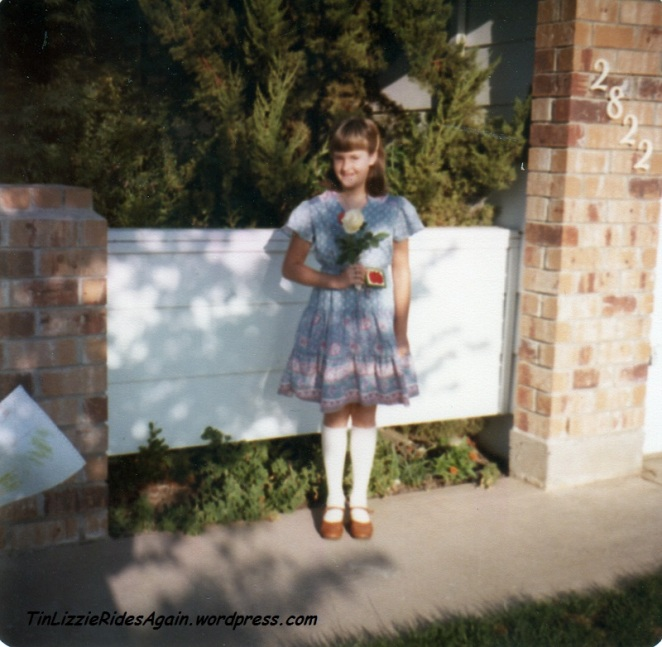 Fourth Grade and the photos move outside. I'm clutching camellias from the yard, for the teacher I assume. Another floral dress and knee socks again.
